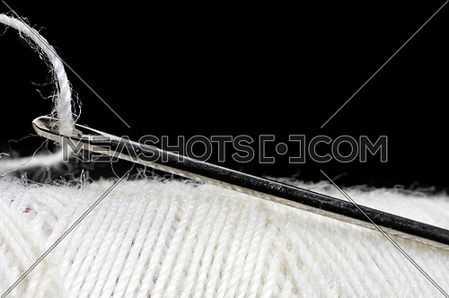 macro shot of needle and thread over black background