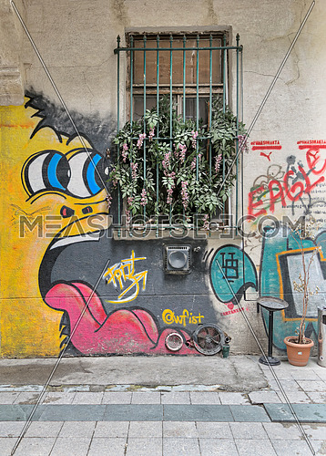 Istanbul, Turkey - April 18, 2017:  Abandoned gruge wall with closed window and colorful graffiti near Istiklal Street