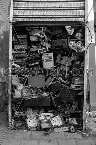 a black and white image of Old radios and electronic devices stacked on top of each other in a kiosk