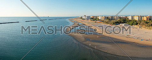 Aerial view of sandy beach with umbrellas and gazebos.Summer vacation concept.Lido Adriano town,Adriatic coast, Emilia Romagna,Italy.
