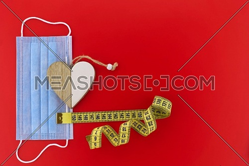 Social Distancing concept - wooden heart medallion of two separate sides placed on medical face mask next to a tape measure, all isolated on red background