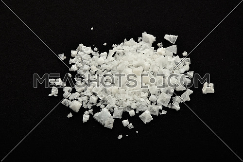 Handful of white Cyprian pyramid sea salt isolated on black paper background