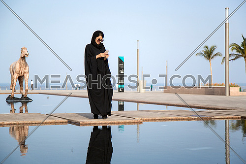 Saudi Lady using her phone at day.