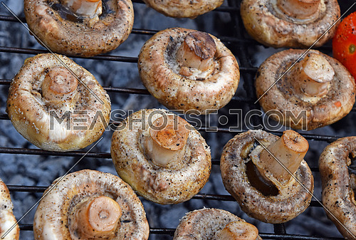 White champignons portobello mushrooms being cooked on char grill, close up