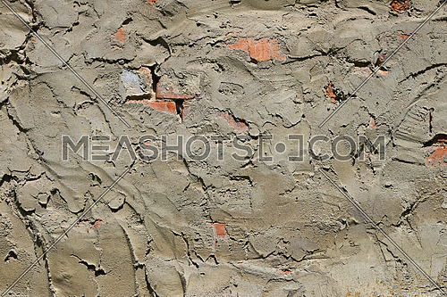 Cement uneven rough plastering layer on unfinished brick wall of construction site