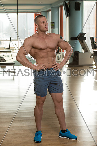 Serious Man Standing In The Gym And Flexing Muscles