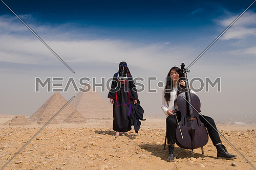 famale chello player and woman in traditional egyptian clothes in  ftont of pyramids