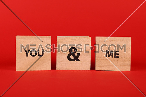 Close up three wooden cube signs with YOU AND ME words over red background with copy space, low angle side view
