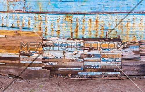 Exterior of paneled aged wooden wall with shabby cracked painting on sandy shore