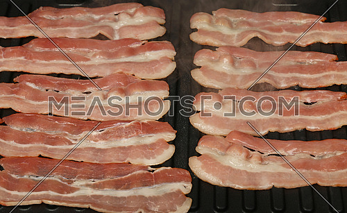 Close up cooking several bacon slices, rashers, on electric grill surface, high angle view