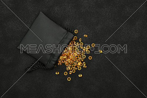 Close up heap of golden yellow rhinestone crystals spilling out of leather bag over black background, elevated top view, directly above