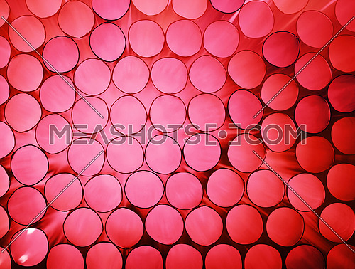 Abstract coral color toned pink background texture of backlit stack drinking straw circles