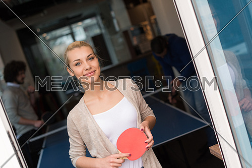 group of young startup business people playing ping pong tennis at modern creative office