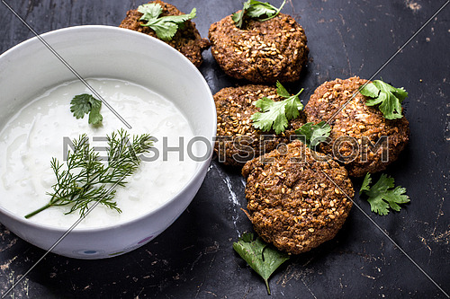 Falafel put on a table top beside a bowl of yogurt Falafel is a traditional Middle Eastern food, commonly served in a pita, which acts as a pocket, or wrapped in a flatbread known as tameya