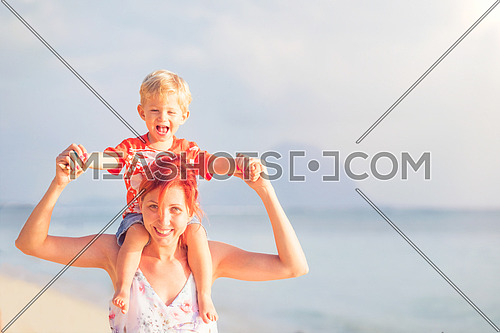 Happy baby boy sitting on shoulders of mother on beach.