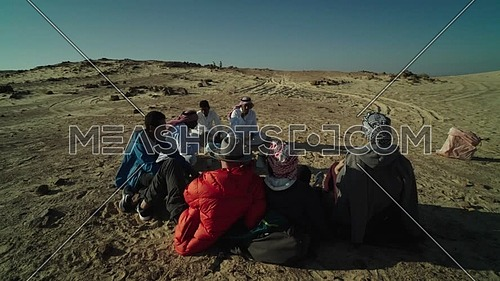 Follow shot for group of tourists sitting with bedouin guides exploring Sinai Trail from Ain Hodouda at day.