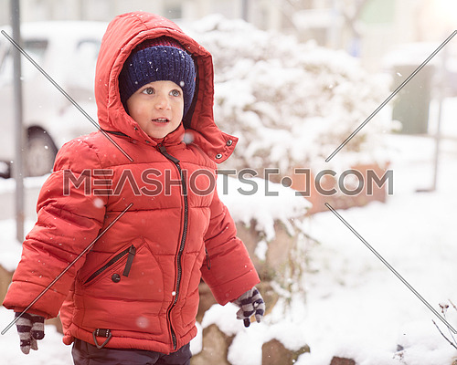 Kid boy while it snows looks towards the emptiness, covered with red winter jacket and woolen hat.