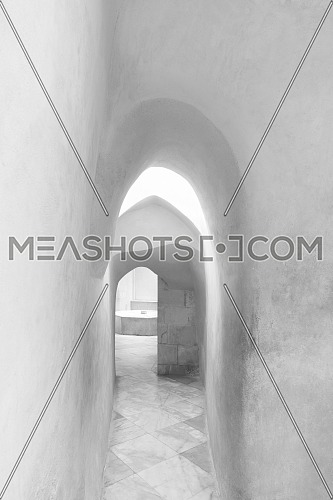 Black and white narrow archway of aged building with smooth shabby walls and tiled floor