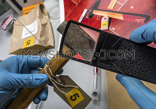 Expert police examines with magnifying glass a hammer in laboratory forensic equipment, conceptual image
