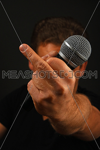 Male hand holding microphone with finger fuck off insult ignore gesture with head behind on black background