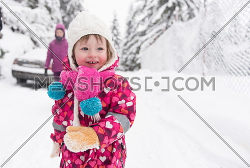 portrait of happy smiling little girl child outdoors having fun and playing on snowy winter day