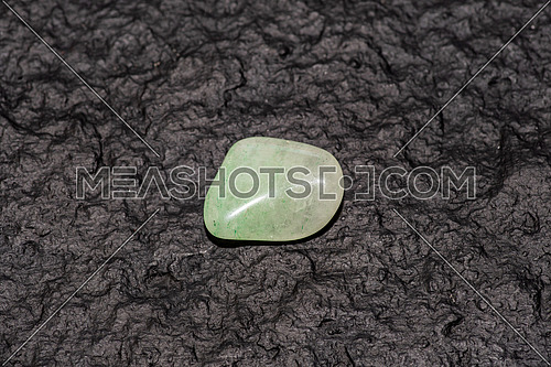 Green aventurine gem stone isolated on black stone background. Macro shot