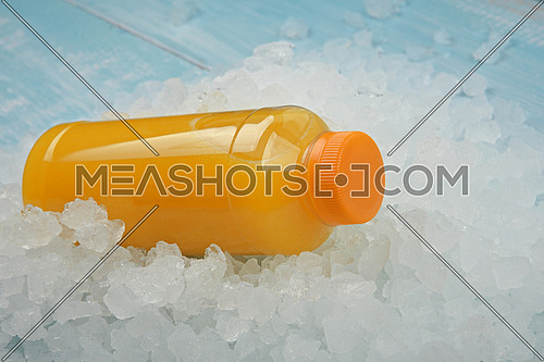 Close up one plastic PET bottle of fresh orange juice over background of crushed ice, high angle view