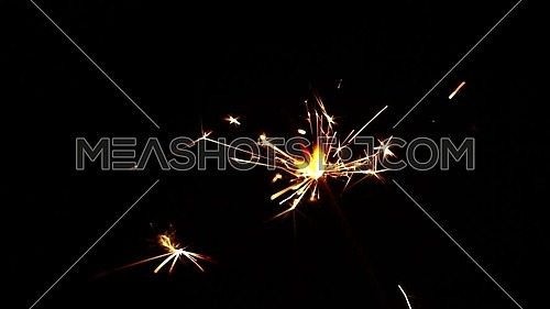 Close up one firework sparkler over black background, low angle side view