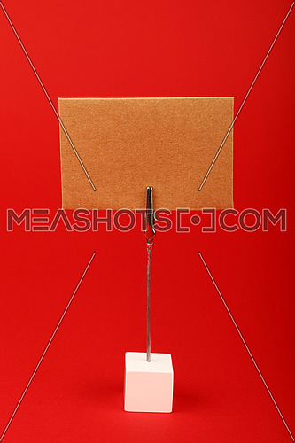 Blank brown kraft cardboard paper parchment sign with copy space on metal and wooden note holder over red background, front side view