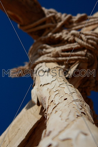 a wooden pillar tied by ropes
