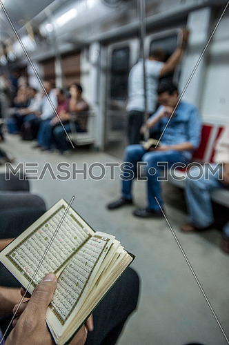 A man reading the Quran in the Metro