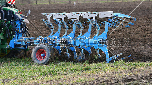Harrowing and plowing equipment in tow by tractor