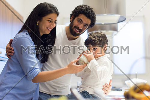 young middle east father and mother with son spend cheerful time in the kitchen
