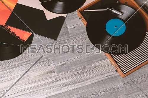 Vintage Gramophone with a vinyl record on gray wooden table, top view and copy space.