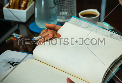 girl hands holding a book in a coffee shop