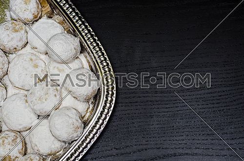 Kahk seted up on a silver plate ready to get served on a black wooden background