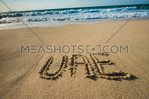 in the picture at the beach  written on the sand UAE