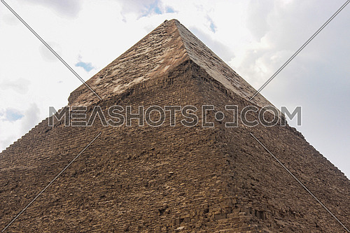 a photo from the Pyramids area showing a view of one pyramid from down to top and blocks , layer covering the top ,  stones used in the architecture