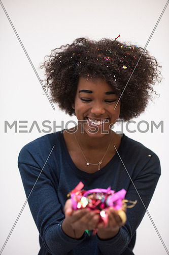 beautiful young black woman celebrating new year and chrismas party while blowing confetti decorations to camera