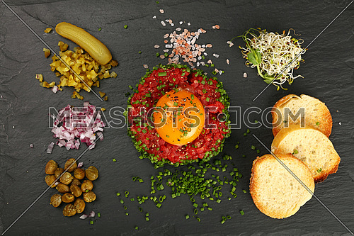 One portion of raw minced beef meat tartare steak with egg yolk, green shallot onions, cucumbers, capers, salt and toasts served on black slate board, close up, elevated top view, directly above