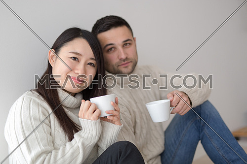 happy young multiethnic couple enjoying morning coffee by the window on cold winter day at home