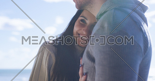 Cool Couple Laughing and hugging In Front Of Beach at beautiful autumn day