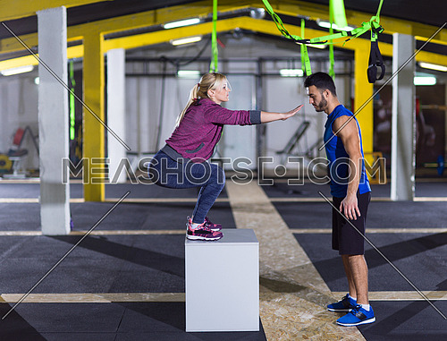 young athletic woman training with personal trainer  jumping on fit box at crossfitness gym