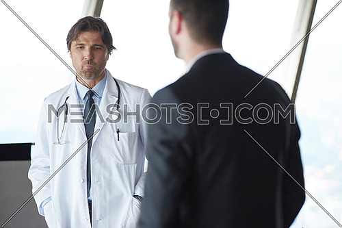 doctor handshake with a patient at doctors bright modern office in hospital