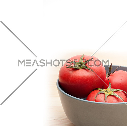 fresh ripe tomatoes on a blue bowl over pine wood table