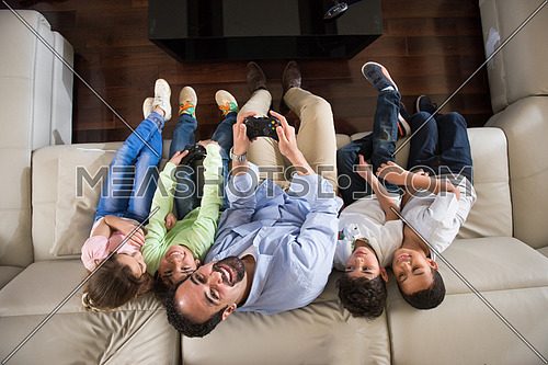 middle eastern man enjoys playing video games with the kids on the sofa