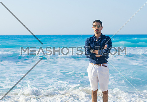 a young man standing by the blue sea
