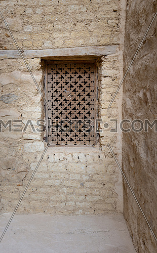 Ancient wooden window with geometrical pattern based on the christian cross on external brick stone wall at Saint Paul the Anchorite Monastery (Monastery of the Tigers), Red Sea, Egypt