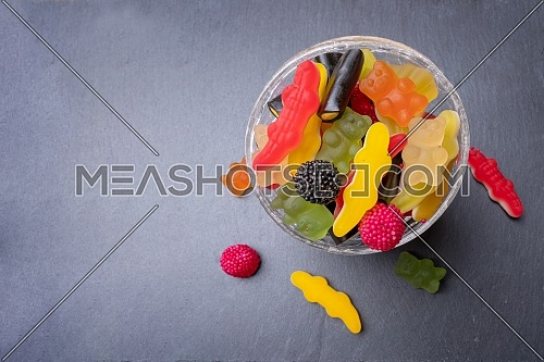 Colored candies inside a glass cup on dark background. Top view with space for your greetings