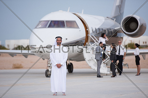 Portrait of a young Arab successful businessman in front of private airplane